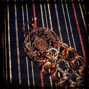 This is a close-up shot of the overly large pendant I chose to use as the focal point of my dress uniform military decoration chain. In the photo above this one, you can see a few small metal scales I added to the end of each chain and at the point where the three chains will hook to one of the buttons on the jacket. In this photo, you can also see the different chains, 2 of which are brass double-cable chains and one of which is made of the two different kinds of star washers I could find. I made the star washer chain but not the other two. I added a pendant bail to the top of the focal pendant so I should be able to attach it much more easily to the jacket. I hope!