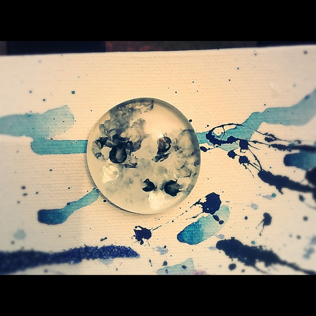 I created this moon using a large, flat-backed glass pebble and some fingernail polish. Oh! I forgot to mention I used an old pencil with the eraser worn down to create the texture effect you see. Black was a second choice. I couldn't find my gunmetal grey nail polish. After I got the white/grey/black/ice blue blend I wanted, I let the pebble dry. I then coated the entire back with white. I set the pebble in place with E-6000.