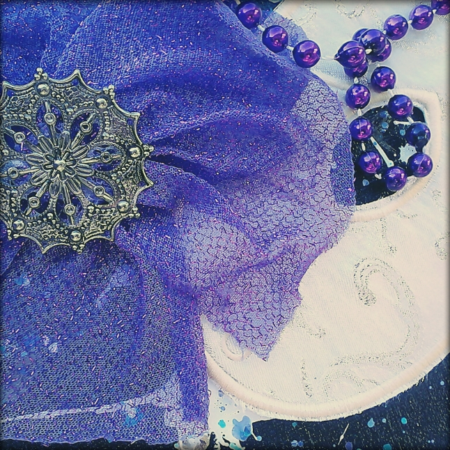 Here's a close-up of the feminine mask, showing the purple sparkle mesh flower, the filigree jewelry finding, and the purple bead. You can also see more of the scroll pattern on the mask. This one is embroidered in pale gold.