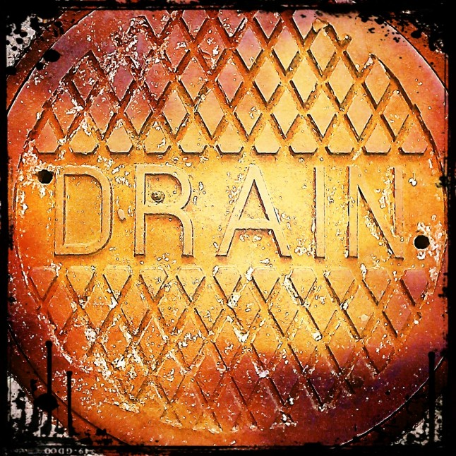 I noticed this drain cover had a word on it so I snapped a photo with my phone. I edited it with the Pixlr-O-Matic app for Android.