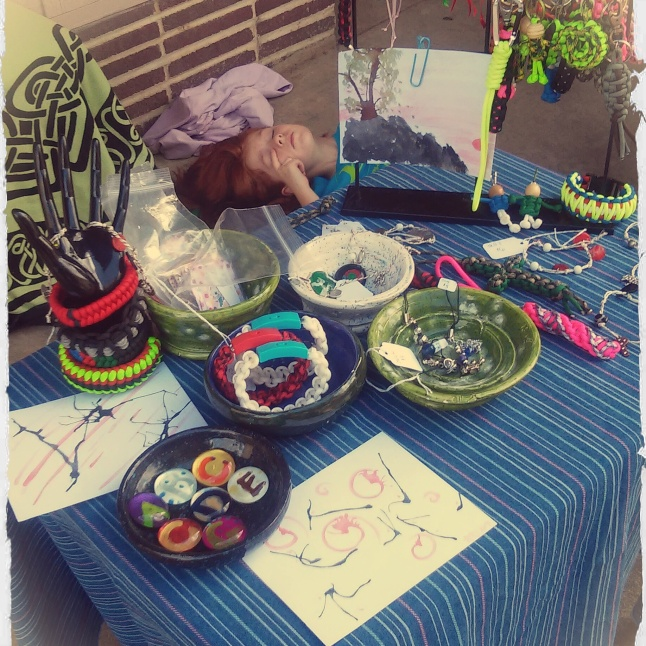This is our small table set up for the Farmer's Market. I didn't put out much of my chainmail today. Most of our items were John's paracord items he's been experimenting with. We also had the girls' painted glass stones on our table and my three paintings as I completed them. You can get a better idea of the small size of the paintings in this picture. I took this picture with my cell and edited it in Pixlr Express, an Android app.